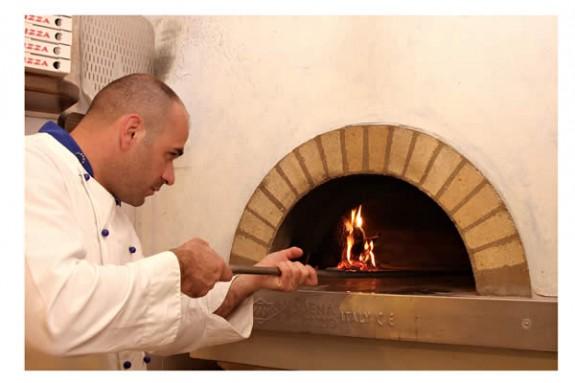 Här tillagas pizzan i vedeldad ugn