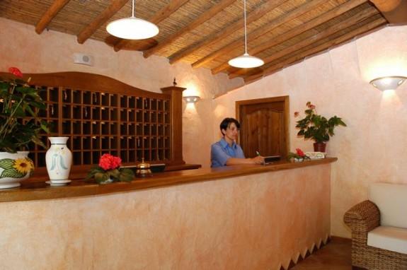 Receptionen i Hotel L'Esagono. Arkitekturen är typiskt sardisk med naturmaterial och putsade väggar i ljusa färger.