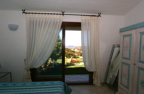 Sovrum med dubbelsäng och utsikt över bergen och havet.